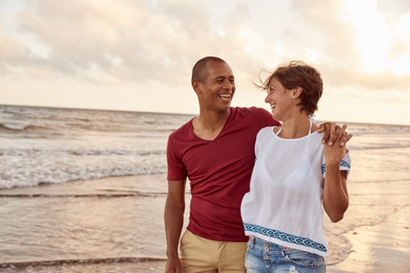 Joyfully laughing embracing couple in love looking at each other on the beach shore while enjoying the breaking waves around their feet