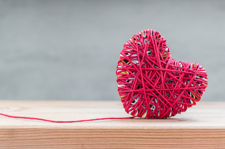 Foto de Read heart yarn on wood table over grunge cement background - Imagen libre de derechos
