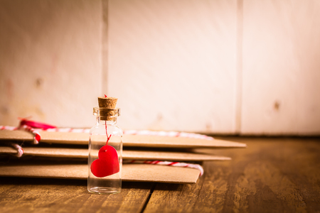 Photo for Love heart message in a bottle with envelope on wood table , vintage tone - Royalty Free Image