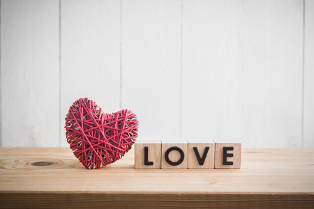 Photo pour Red heart yarn with love in cube on wood table - image libre de droit
