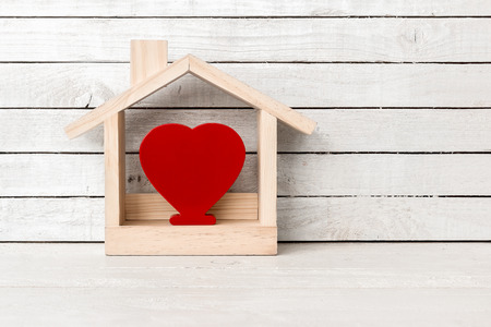 Photo pour Wood Home Shaped with red heart shaped on white wood over white wood background. - image libre de droit