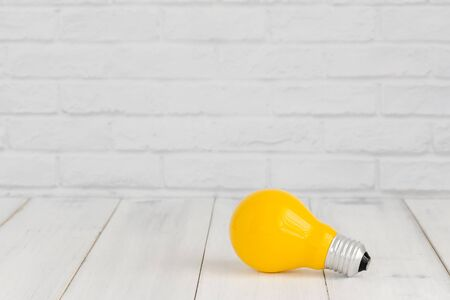 Photo for Yellow light bulb on white wood table over white brick background with copy space. - Royalty Free Image