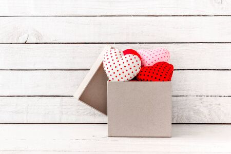 Photo pour Many Red Heart Shaped with brown gift box over white wood background - image libre de droit