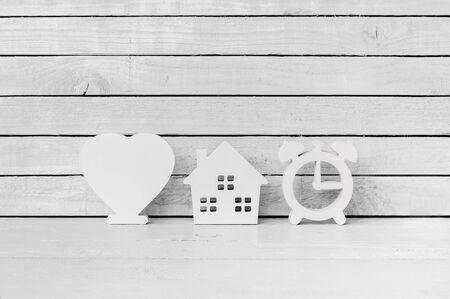 Photo pour White Heart Shaped with Clock Shaped and Home Shaped on white wood over white wood background - image libre de droit