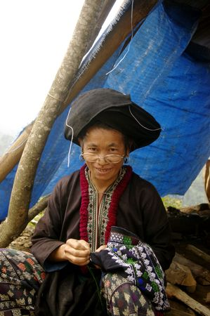 Dao tribe woman embroidering black pants. The reasons are rituals and art is always the same for centuries.