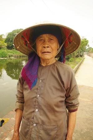 Grand-mÚre «Kinh» devant le bassin de La Pagode