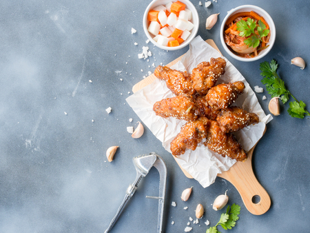 Deep fried chicken wing with garlic sauce in Korean style serve with kimchi and pickled radish on grey background in top view with copy space  for asian food concept.
