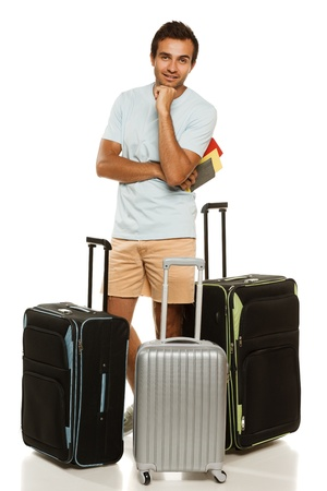 Full length of young man standing with three travel suitcase, holding passport with tickets, against white background