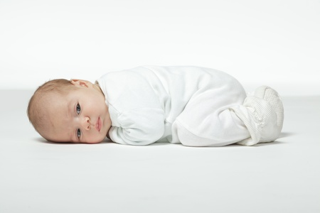 Photo pour Newborn baby curled up lying on his stomach - image libre de droit