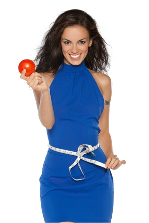 Pretty smiling woman in blue dress measuring waist with measurement type, holding a tomato, isolated on white
