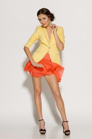Full length of fashion model posing in mini skirt fluttering on the wind