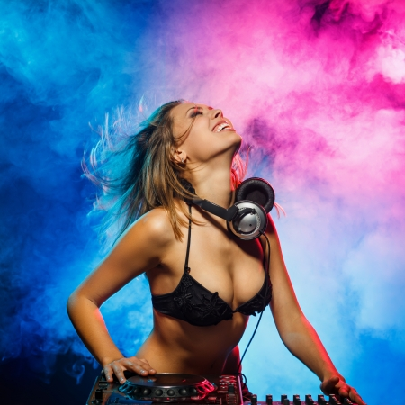 Photo for Excited DJ girl on decks on the party - Royalty Free Image