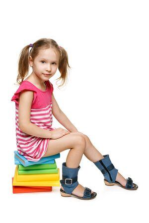 Little preschool girl sitting on the stack of books, in full length, over white background