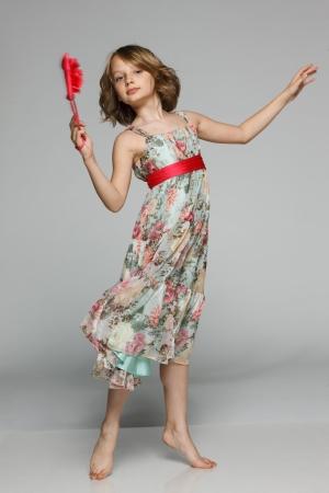 Little girl dancing in studio wearing light chiffon dress, over gray background