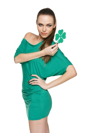 Woman wearing green dress showing artificial green shamrock leaf against white  background