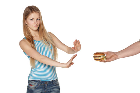 Discontent young female refusing fast food, against white background