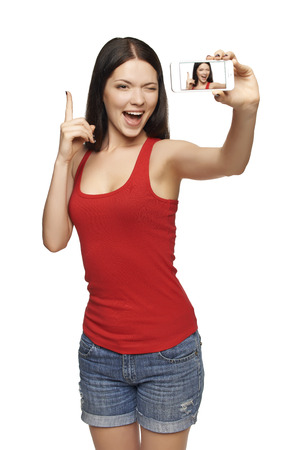 Happy excited young woman with finger up, while taking pictures of herself through cell phone, over white background