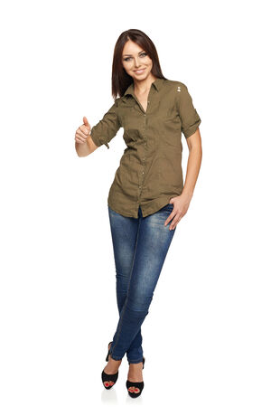 Full length of young smiling female in jeans and green shirt giving you thumb up over white background