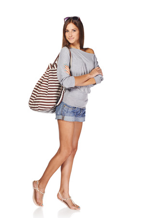 Photo for Full length of smiling young slim tanned female in denim shorts with backpack and sunglasses, isolated on white background - Royalty Free Image