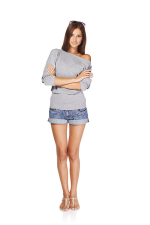 Full length of young stylish slim tanned female in denim shorts standing with folded hands, isolated on white background