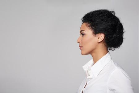 Closeup profile of confident business woman looking forward isolated on gray backgroundの写真素材