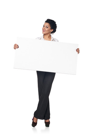 Full length smiling business woman holding blank white board, isolated on white background
