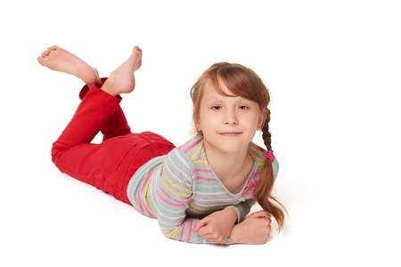 Front view of smiling child girl lying on stomach on the floor looking at camera smiling, over white background