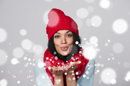 Christmas Girl. Mixed race african american - caucasian woman wearing knitted warm scarf and hat blowing snow at you, looking at camera, over gray backgroundの写真素材