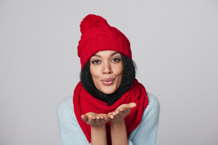 Christmas Girl. Mixed race african american - caucasian woman wearing knitted warm scarf and hat blowing a kiss, looking at camera, over gray background