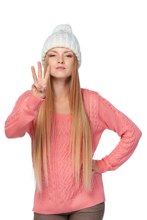 Hand counting - three fingers. Portrait of woman on white background wearing woolen hat and sweate showing three fingers