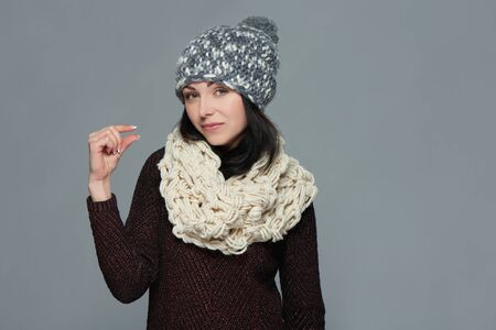 Woman wearing warm winter clothing indicating little bit, over grey background