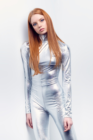 Futuristic young woman in silver clothing standing leaning at wall. Sci-fi style.