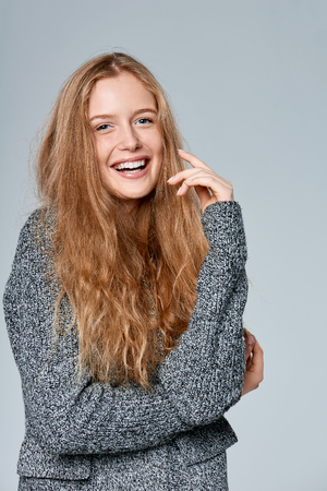 Photo pour Happy laughing beautiful woman muffling in warm knitted cardigan, over gray background - image libre de droit