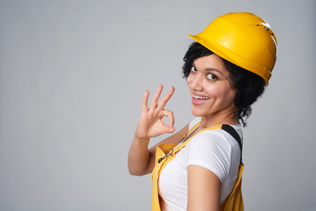 Smiling mixed race construction woman wearing yellow protect helmet and overall showing OK gesture over shoulder, over grey background