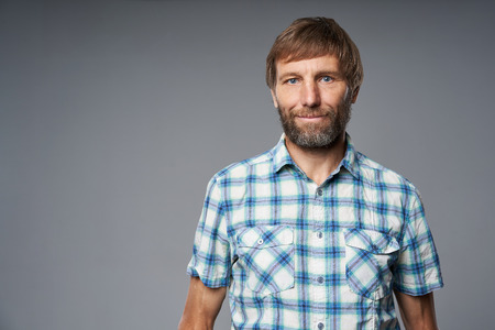 Photo pour Portrait of mature man in checkered shirt looking at camera, over grey studio background - image libre de droit