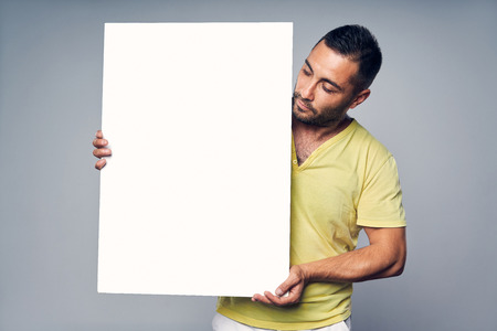 Photo pour Man holding blank white board with copy space for text, looking at board, over gray background - image libre de droit