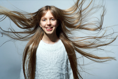 Photo for Teen girl with long hair flying in air, over studio grey background - Royalty Free Image