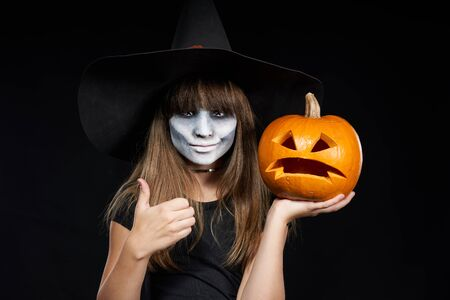 Foto de Halloween witch girl showing Jack-O-Lantern pumpkin on palm and giving thumb up looking at camera on black background. Preteen girl with terrifying makeup and witch hat. - Imagen libre de derechos