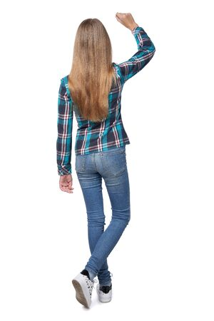 Foto de Full length back view of teen girl in checkered shirt standing casually over white background writing on the blank copy space - Imagen libre de derechos