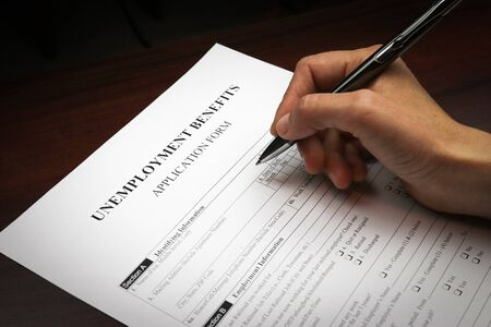 Photo for Close-up of a person's hand filing social security benefits application form. - Royalty Free Image