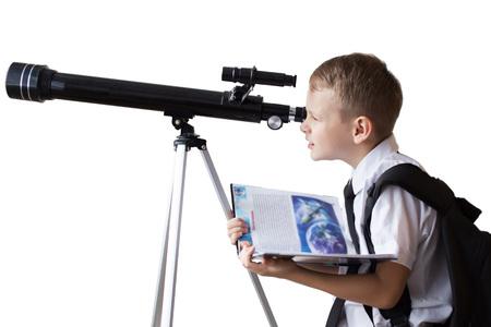 Photo pour Schoolboy looking through a telescope on a white background - image libre de droit