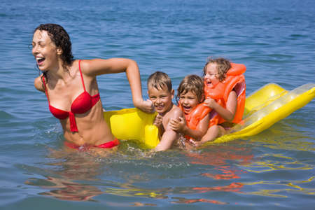 young woman rolls three children on an inflatable mattress in sea