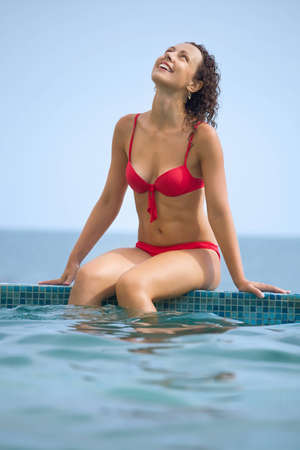 young beautiful sexual woman sitting on ledge pool on resort against sea