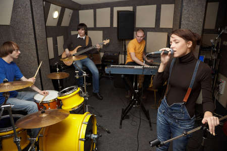 a rock band working in studio. vocalist girl is singing. focus on clothers of vocalist girl