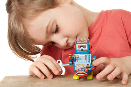 little girl in red T-shirt plays with clockwork robot isolated on white background