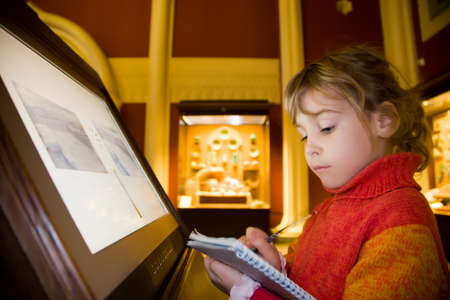 little girl standing near monitor writes to writing-books at excursion in historical museum against exhibits of ancient relics in glass cases
