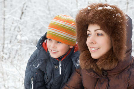 smiling pretty woman and cheerful boy in winter in wood