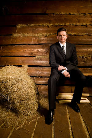 businessman sitting on bench near haystack in wooden log hut, looking in camera