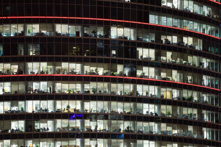 modern office building with big windows at night, in windows light shines