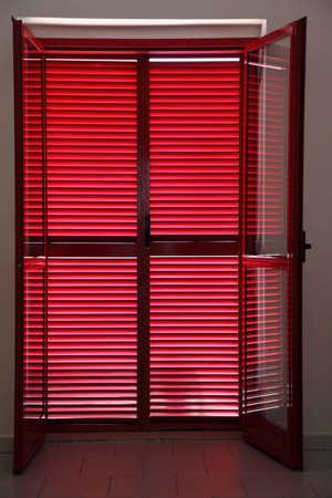 Door on  verandah which is closed red jalousies